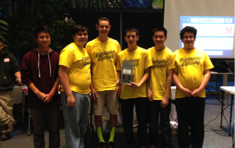 Robotics team members pose with their award.