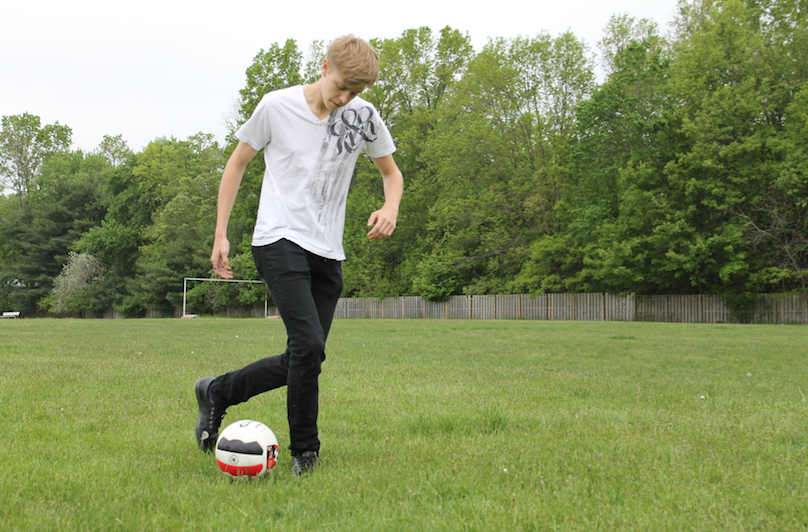 Burmood kicks a soccer ball.
