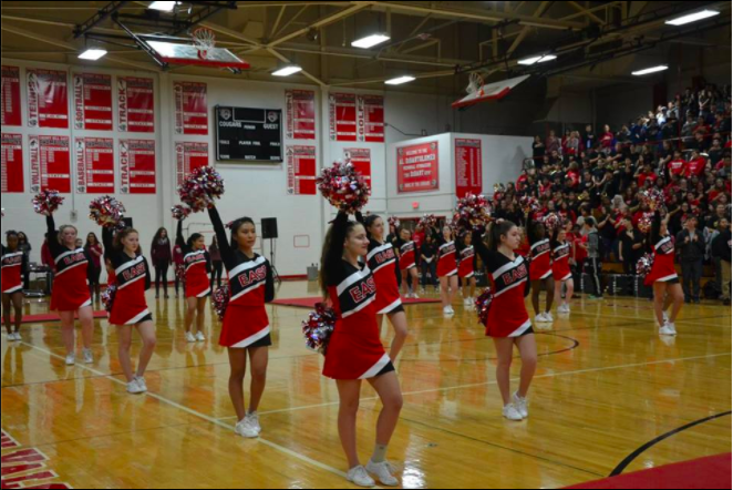The cheerleaders welcome students as they enter the DiBart Gym.