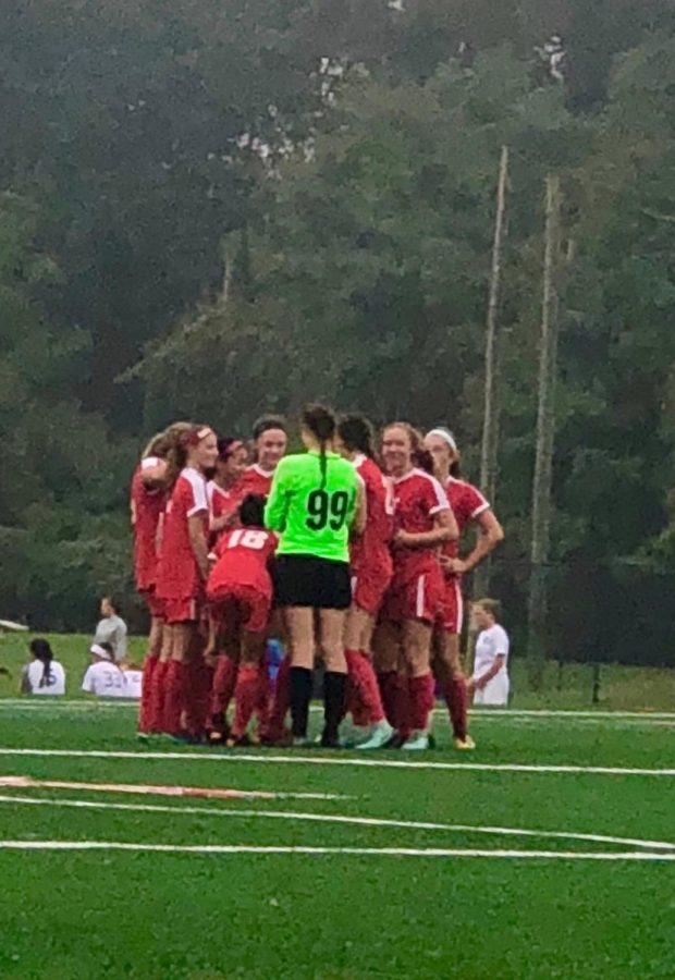 Girls soccer team huddles before the game.