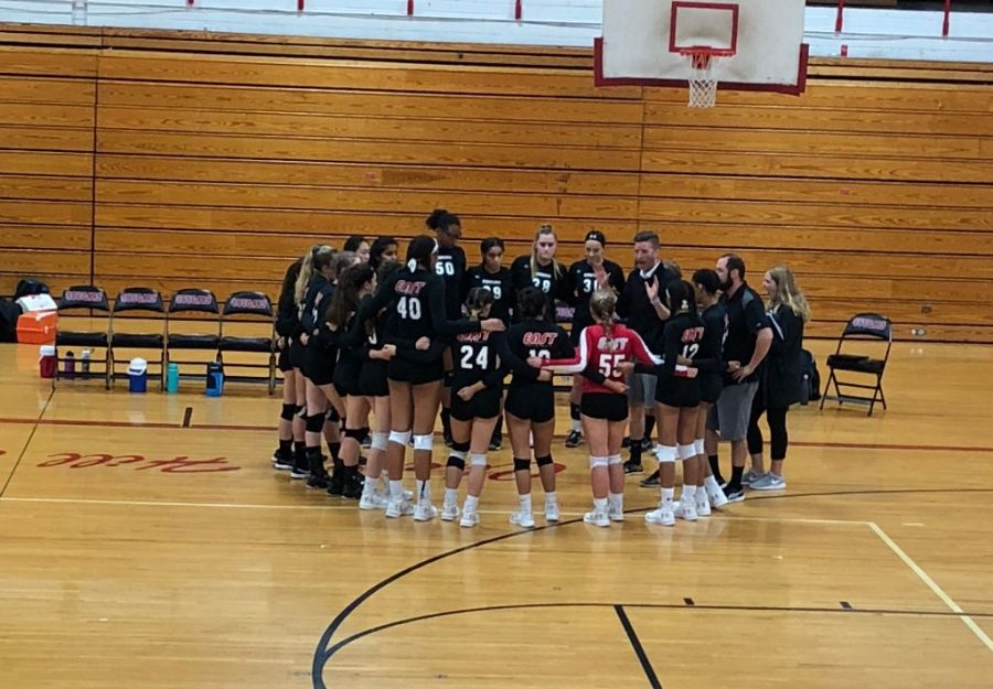 Girls+volleyball+team+huddles++with+coaches+to+discuss+strategies.+