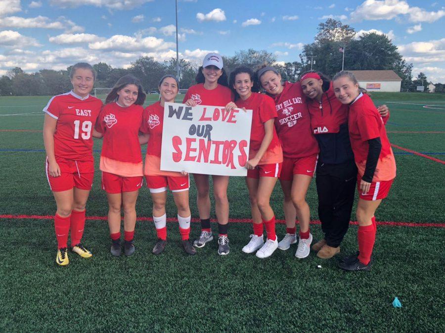 Girls+soccer+team+seniors+smile+for+a+picture+on+Senior+Day.