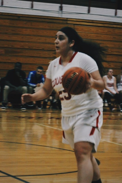 Yaya Villegas ('20) dribbles the ball to the basket.
