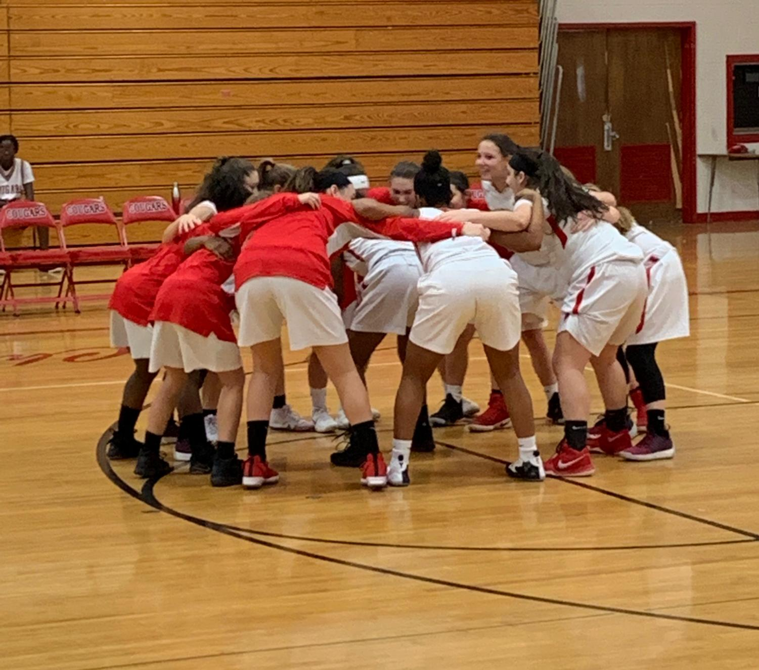 The East Girls Basketball players huddle before the game.