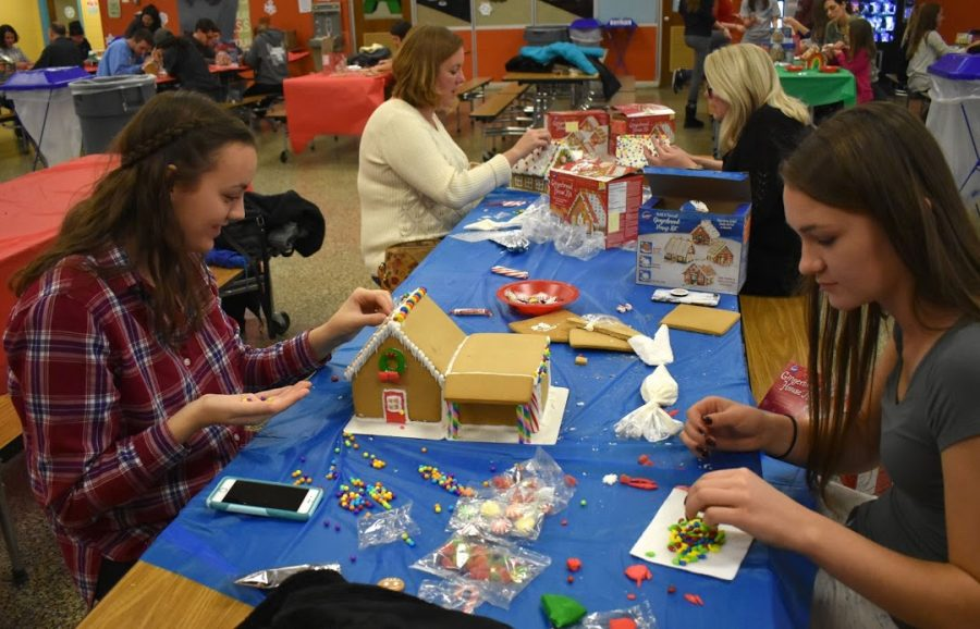 Students from Habitat for Humanity participate in a gingerbread house making activity.