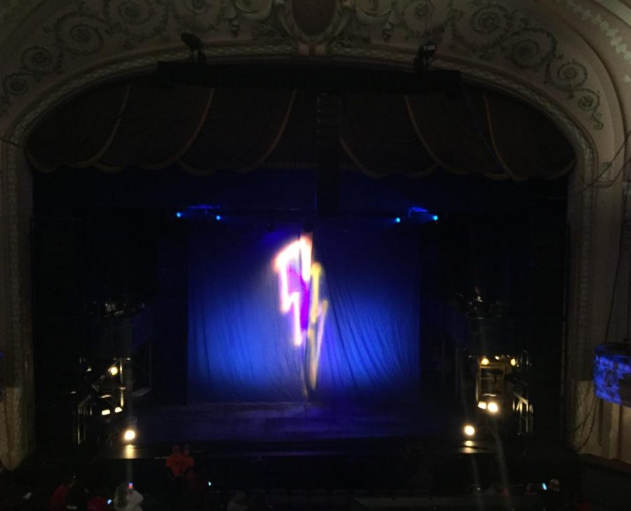 A lighting bolt is projected on the curtains before the show starts.