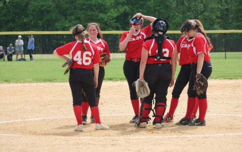 The girls talk things over on the mound.