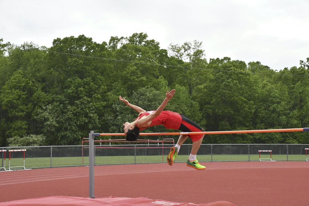 An East boys' track player jumps backwards over a bar.