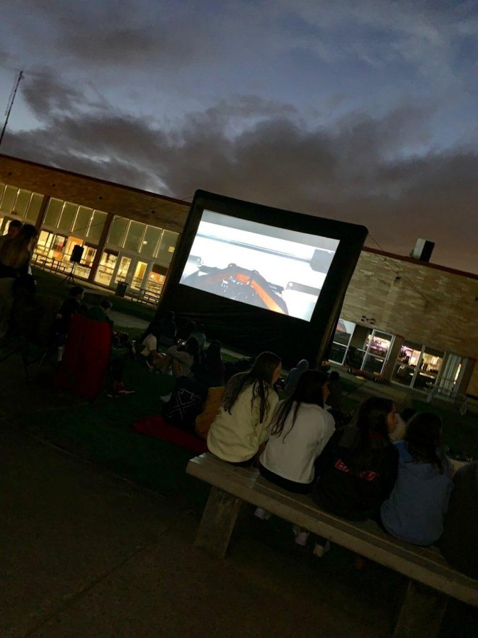 East+community+members+gather+in+the+courtyard+to+watch+Jaws.%0A