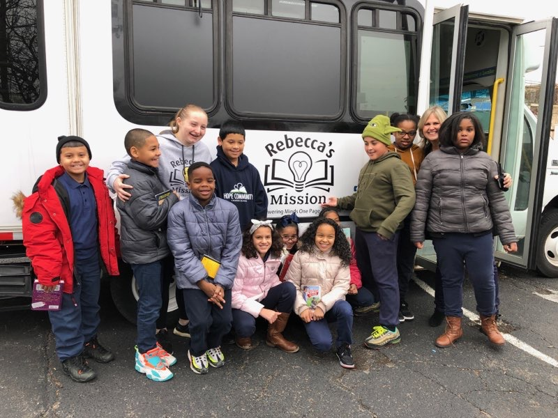 Benjamin and students pose in front of the bookmobile