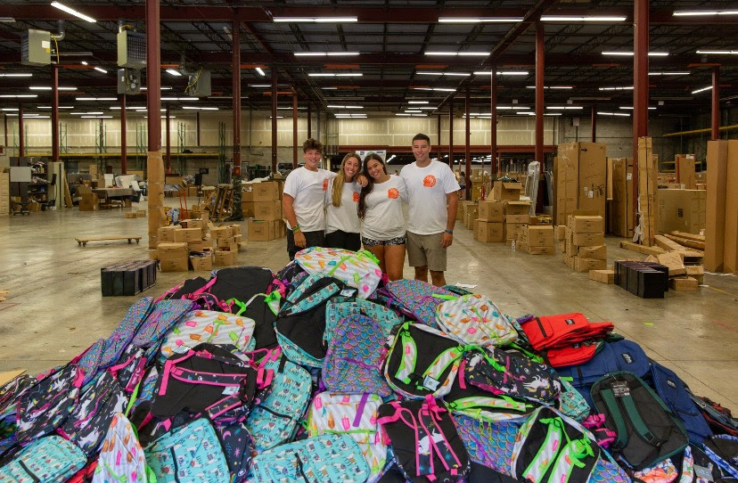 The Checkoffs gather near backpacks for the nonprofit.