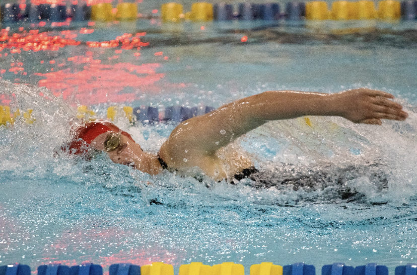 Annie Behm ('21) swims her way to victory at a meet for East in the backstroke.