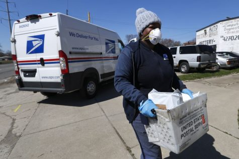 USPS worker carries a box of mail while wearing a mask