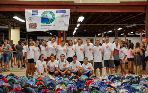 Volunteers gather in front of the backpacks that were packed during last years event.