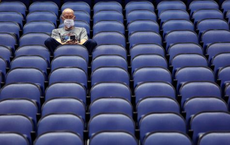 Fan sits alone in an empty Greensboro Coliseum after the NCAA college basketball games were canceled at the Atlantic Coast Conference tournament.