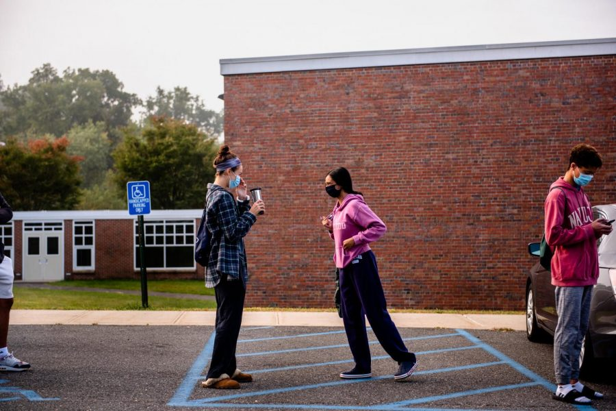 Students wear masks before entering school to take the SAT.