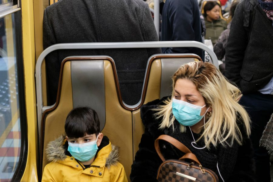A mother and son wear masks while sitting in a bus.
