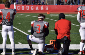 Cherry Hill East assistant football coach Lynell Payne kneels next to senior Nick Tomasselo before a game against Paul VI.