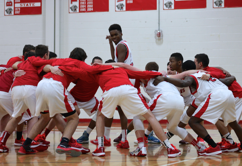 Team members gather around Pierce Elliot ('16) for pre game hype up.