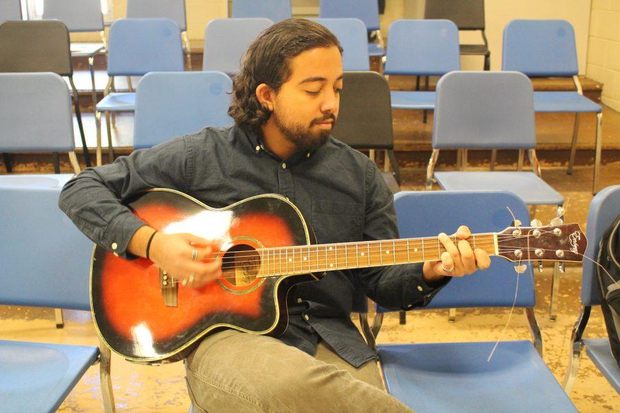 Parsi plays guitar.
