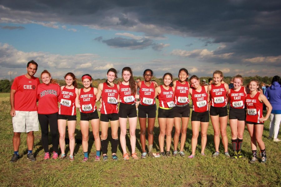 Members of the East girls' cross country team pose with Coach Anthony Maniscalco after winning the South Jersey Olympic Conference Championship.