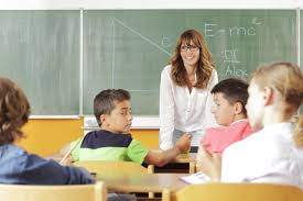 Teacher stands at the front of the class during a lesson.