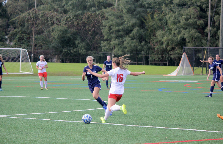 Wons passes the ball to one of her East teammates.