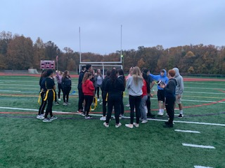 The senior girls gather on the field, with their coaches, to discuss strategies for the 2019 Powder Puff.