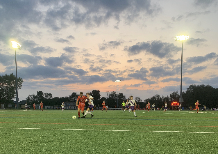 The East Cougars and the West Lions fight for the ball, on the soccer field.