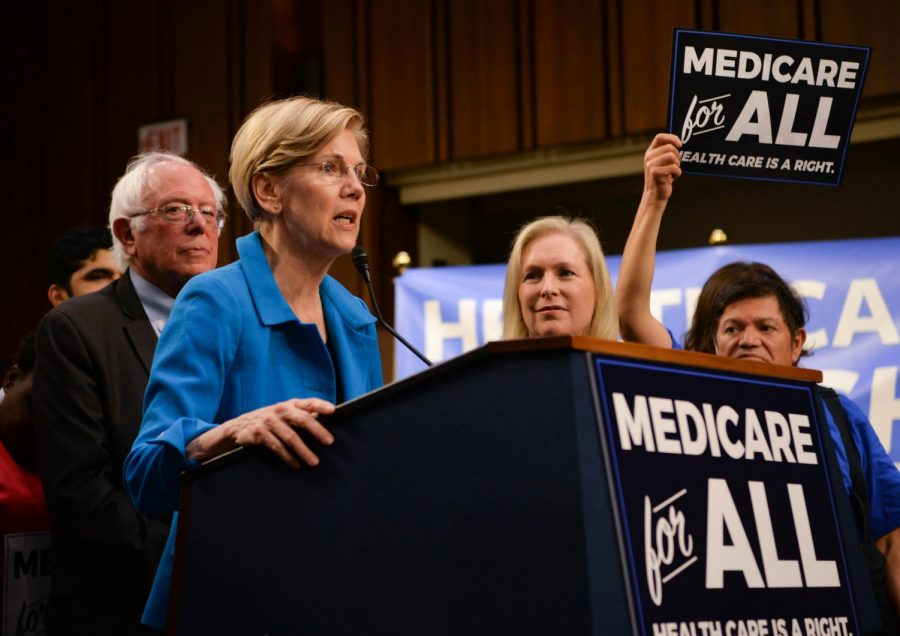 Sanders and Warren display support for medicare for all in front of supporting crowd.