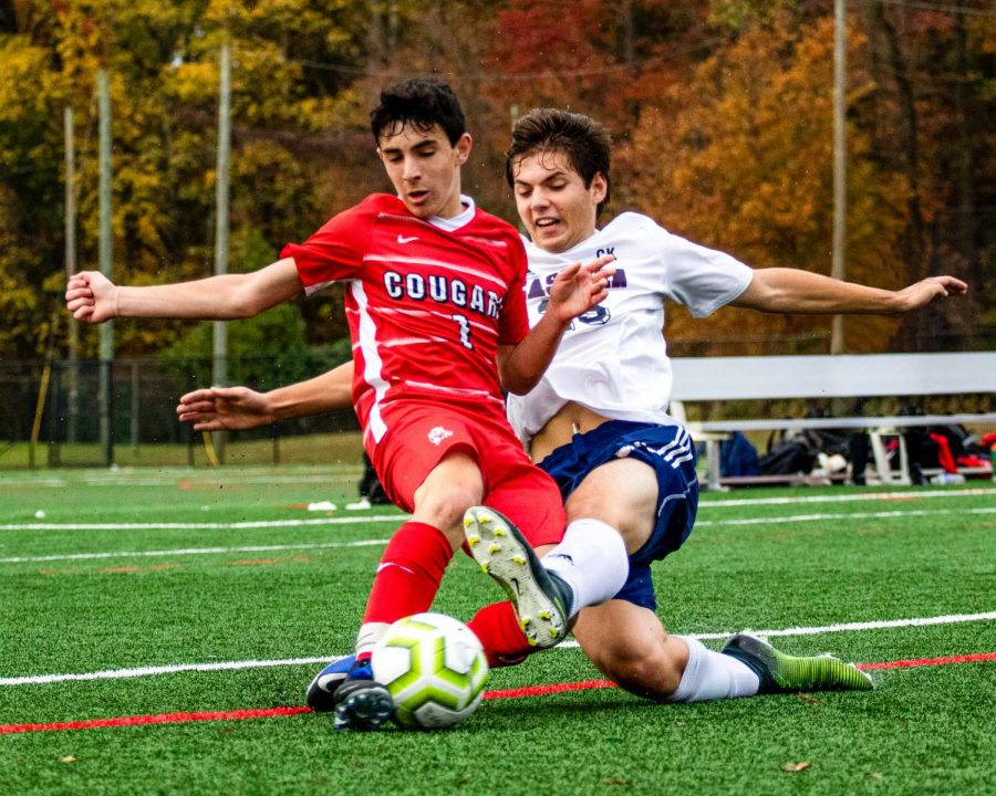 Adam Blumenthal ('23) fights for the ball in the Cougars' playoff match against Toms River North.