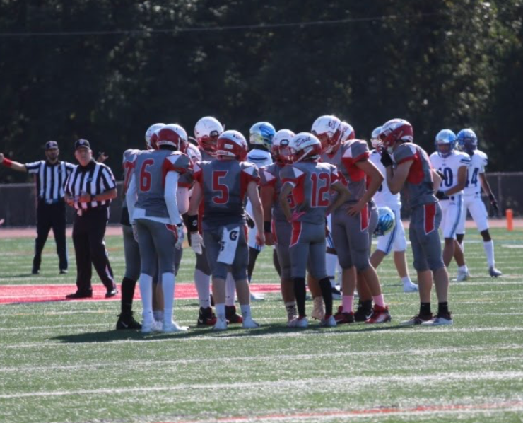 The East football team gathers in a huddle to discuss strategies for the next play.