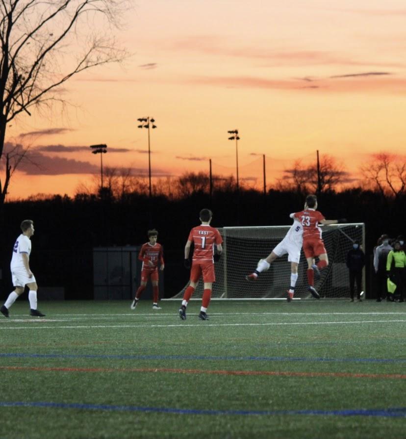 Sophomore Evan Pfeiffenberger rises for a header as the sun sets behind the turf fields at Decou Sports Complex.