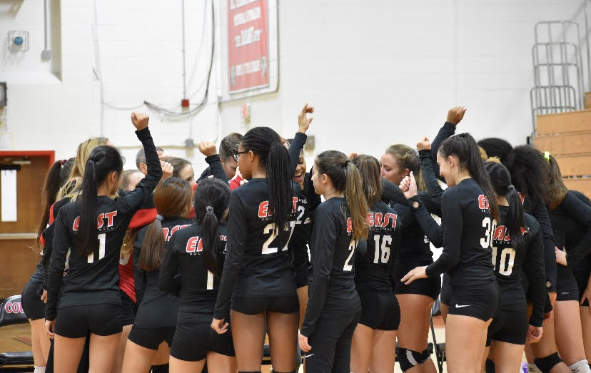 The Cherry Hill East Girls Volleyball team participate in a group huddle before their varsity game.