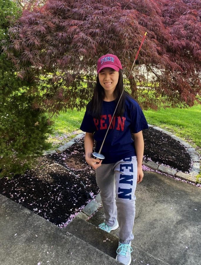 Justina Lam poses in her UPenn college gear alongside the equipment that led her to become a Junior Olympic Silver Medalist in the sport of fencing.